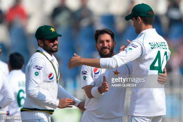 Pakistan's bowler Yasir Shah celebrates with captain Azhar Ali and Shaheen Shah Afridi after taking last wicket of Bangladesh's Abu Jayed during the...