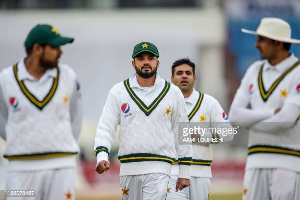 Pakistan's captain Azhar Ali walks back to the pavilion along with teammates after the game has stopped due to bad light conditions during the second...