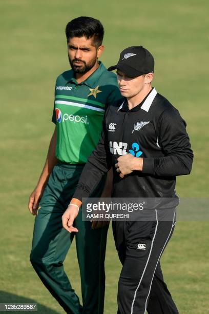 Pakistan's captain Babar Azam and his counterpart New Zealand's Tom Latham arrive during a ceremony at the Rawalpindi Cricket Stadium in Rawalpindi...