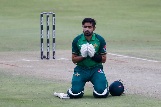 Pakistan's captain Babar Azam kneels down while celebrating after scoring a century during the first one-day international cricket match between...