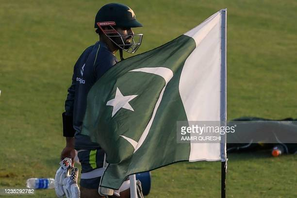 Pakistan's captain Babar Azam walks past a national flag as he arrives to bat during a practice session at the Rawalpindi Cricket Stadium in...