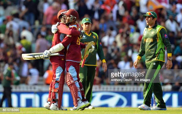 Pakistan's captain MisbahulHaq lookson as West Indies' Kemar Roach and Denesh Ramdin celebrate their victory during the ICC Champions Trophy match at...