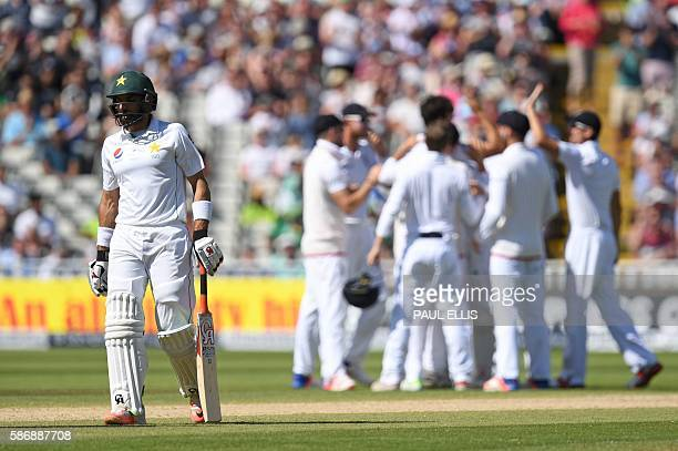 Pakistan's captain MisbahulHaq walks back to the pavilion as England players celebrate during play on the final day of the third test cricket match...