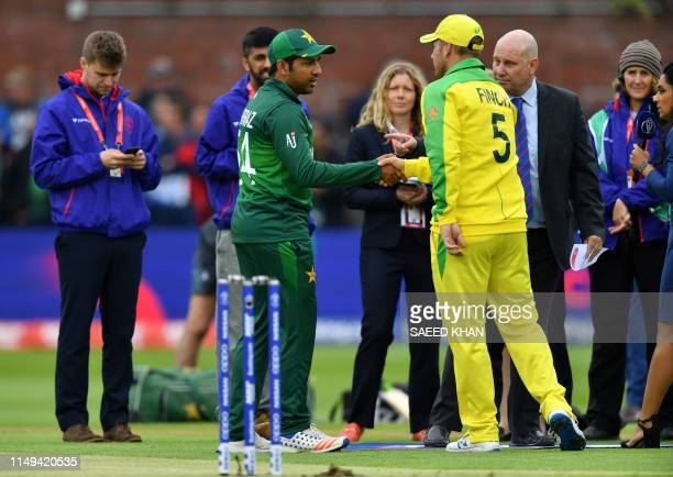 Pakistan's captain Sarfaraz Ahmed shakes hands with Australia's captain Aaron Finch after winning the toss ahead of the 2019 Cricket World Cup group...