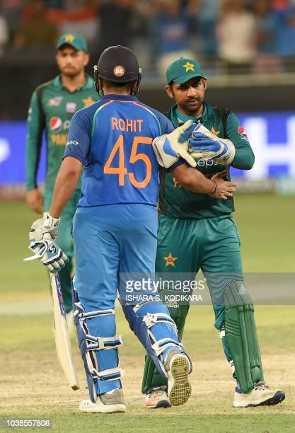 Pakistan's captain Sarfraz Ahmed and Indian team captain Rohit Sharma leave the field after India won by 9 wickets during the one day international...