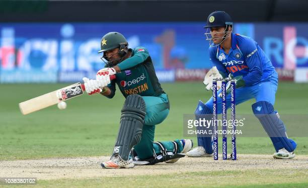 Pakistan's captain Sarfraz Ahmed plays a shot as Indian wicketkeeper Mahendra Singh Dhoni looks on during the one day international Asia Cup cricket...