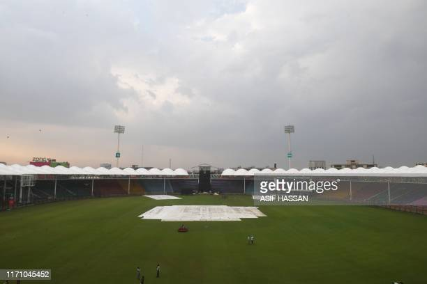 Pakistan's Cricket Board official stand in the National Stadium after the team practice was postponed due to rain in Karachi on September 25 2019