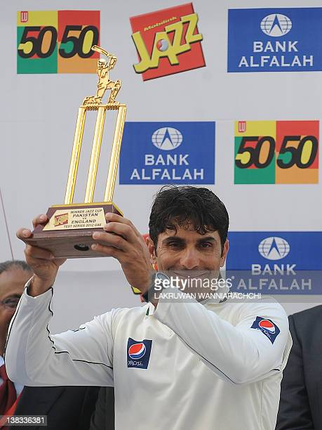Pakistan's cricket captain Misbahul Haq gestures as he holds the trophy after victory in the third and final Test match between Pakistan and England...