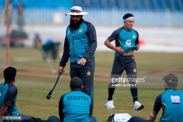 Pakistan's cricket head coach Misbah ul Haq speaks with his cricketers during a practice session at the Pindi Cricket Stadium ahead of the first Test...