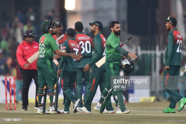 Pakistan's cricket team captain Babar Azam and cricketer Mohammad Hafeez greet with Bangladesh players after winning the second T20 international...