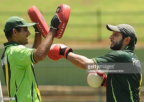 Pakistan's cricket team captain Shahid Afridi punches with teammate Abdul Razzaq during a practice session at the Pallekele International cricket...