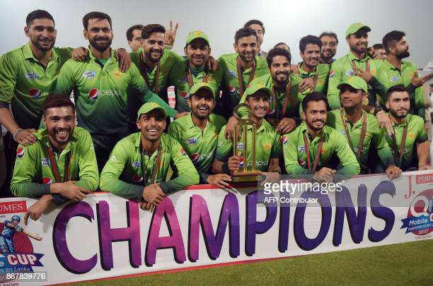 Pakistan's cricket team members pose for photographs with the trophy after winning the third and final T20 cricket match against Sri Lanka, at the...