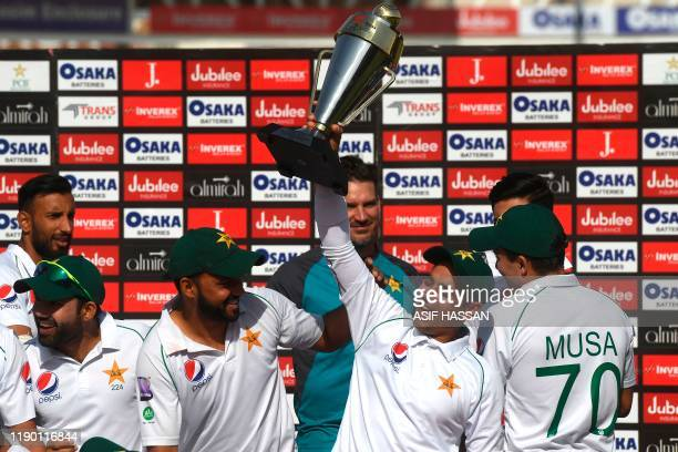 Pakistan's cricketer Abid Ali holds a trophy along with captain Azhar Ali after winning the second Test cricket match between Pakistan and Sri Lanka...