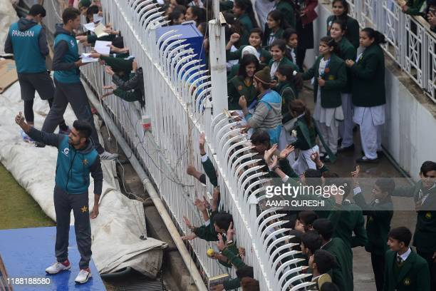 Pakistan's cricketer Babar Azam takes a selfie with fans as the match was delayed due to rain on the third day of the first Test cricket match...