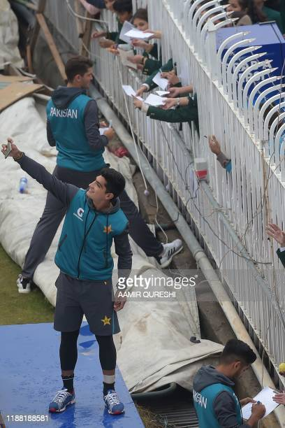 Pakistan's cricketer Naseem Shah takes a selfie with fans as the match was delayed due to rain on the third day of the first Test cricket match...