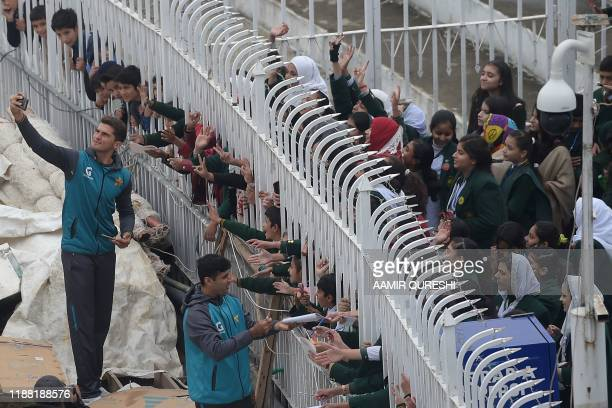 TOPSHOT Pakistan's cricketer Shaheen Shah Afridi takes a selfie with fans as the match was delayed due to rain on the third day of the first Test...