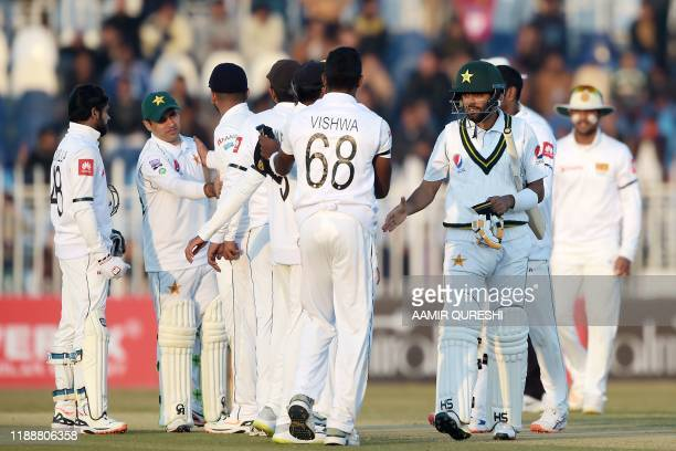 Pakistan's cricketers Babar Azam and Abid Ali shake hands with Sri Lanka's cricketers at the end of the fifth and final day of the first Test cricket...
