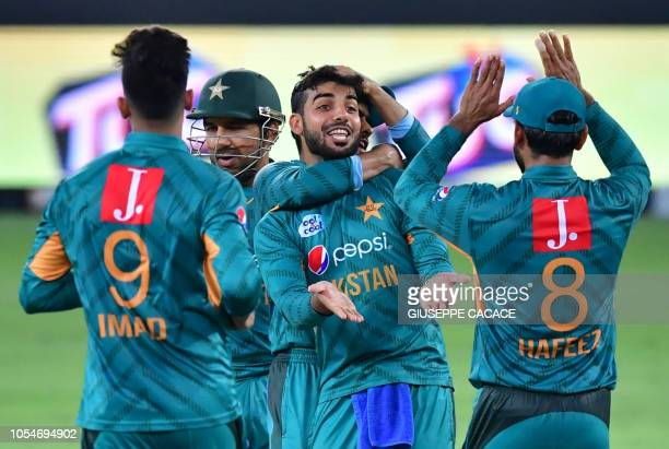 Pakistan's cricketers celebrate after the dismissal of Australian cricketer Chris Lynn during the third T20 cricket match between Pakistan and...