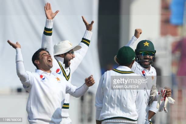 Pakistan's cricketers celebrate after the dismissal of Bangladesh's cricketer Liton Das during the fourth day of the first cricket Test match between...