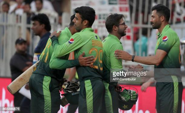 Pakistan's cricketers celebrate their victory at the end of the fifth one day international cricket match between Sri Lanka and Pakistan at Sharjah...