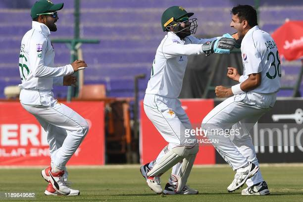 Pakistan's cricketers Mohammad Abbas Mohammad Rizwan and Babar Azam celebrate after the dismissal of Sri Lanka's Niroshan Dickwella during the second...