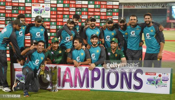 Pakistan's cricketers pose for a photograph with their trophy after winning the third and final one day international cricket match between Pakistan...