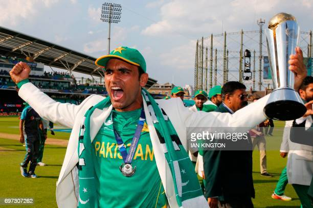 Pakistan's Fakhar Zaman holds the trophy as he celebrates with Pakistan players on the pitch after the ICC Champions Trophy final cricket match...