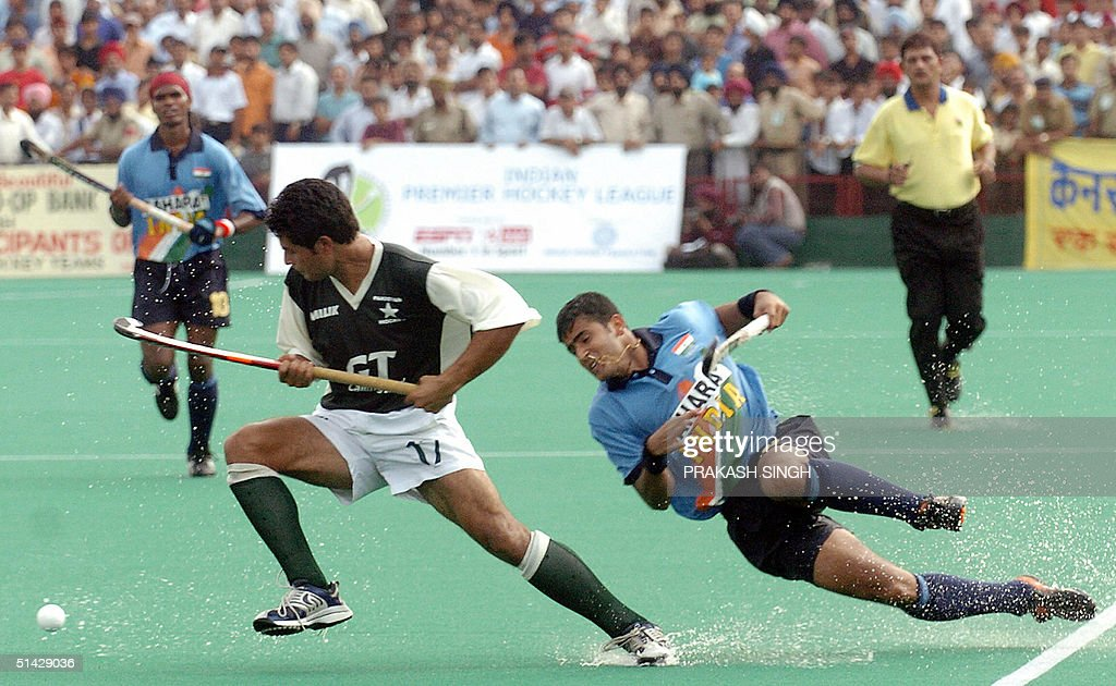 Pakistan`s field hockey player Imran Khan fights for the ball with India`s Tushar Khandekar as India`s Prabodh Tirkey looks on during the sixth match.