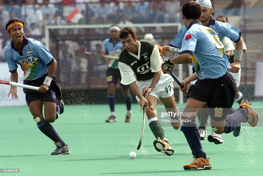 Pakistan`s field hockey player M Shabir is surrounded by India`s Vivek Gupta Viren Rasquniha and Sandeep Singh during the sixth match of the...