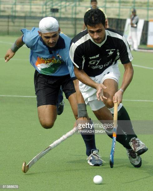 Pakistan's Field Hockey player Rehan Butt and India's Sandeep Singh compete for control of the ball during a match in New Delhi 04 October 2004...
