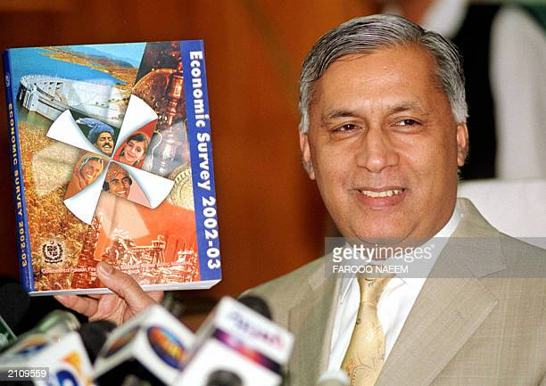 Pakistan's Finance Minister Shaukat Aziz shows a copy of a government economic survey during a press conference in Islamabad 05 June 2003 two days...