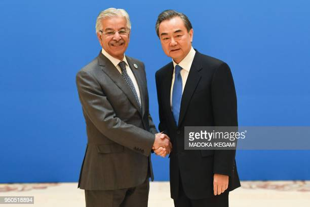 Pakistan's Foreign Minister Khawaja Muhammad Asif shakes hands with Chinese Foreign Minister Wang Yi before a meeting of foreign ministers and...