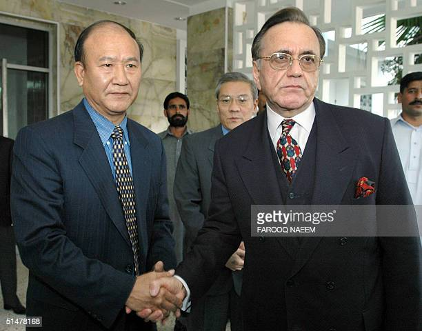 Pakistan's Foreign Minister Khurshid Mahmud Kasuri shakes hands with Chinese Ambassador to Pakistan Zhang Chunxiang at the Chinese Embassy in...