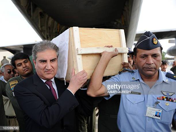 Pakistan's Foreign Minister Shah Mahmood Qureshi and other officials carry the coffin of a Pakistani student Ali Raza, who was killed in ethnic riots...