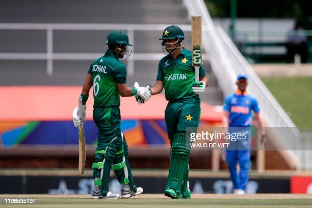 Pakistan's Haider Ali is congratulated by Pakistan's captain Rohail Nazir after scoring a half-century during the semi-final of the ICC Under-19...