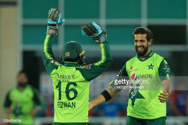 Pakistan's Imad Wasim celebrates with Pakistan's Mohammad Rizwan after England's Captain Eoin Morgan is caught out during the T20 cricket match...