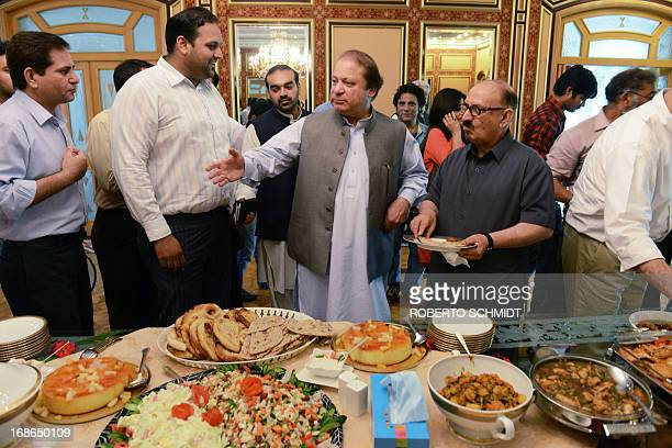 Pakistan's incoming prime minister Nawaz Sharif offers a table full of food to journalists after a press conference at his farm house in Raiwind on...