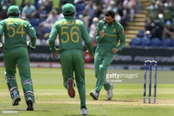 Pakistan's Junaid Khan celebrates with Pakistan's Babar Azam and Pakistan's Sarfraz Ahmed the wicket of England's Jos Buttler during the ICC...