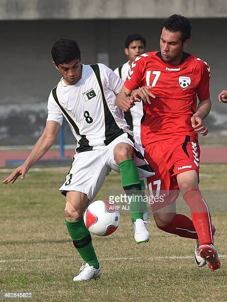 Pakistan's Mehmood Khan vies the ball with Afghanistan's Fardin Hakimi during their friendly football match at the Punjab stadium in Lahore on...