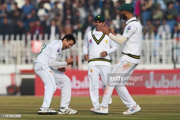 Pakistan's Mohammad Abbas celebrates with teammates after bowing out Sri Lanka's Dinesh Chandimal during the first day of the first Test cricket...