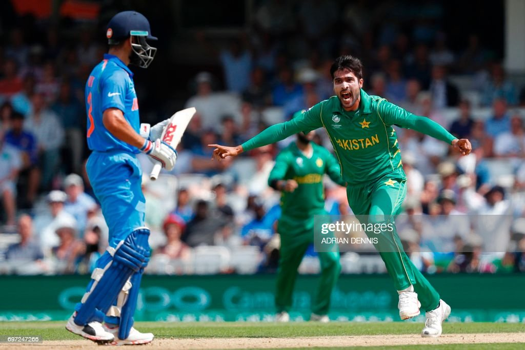 TOPSHOT - Pakistan's Mohammad Amir celebrates after taking the wicket of India's captain Virat Kohli (L) during the ICC Champions Trophy final cricket match between India and Pakistan at The Oval in London on June 18, 2017. Title-holders India were set a target of 339 to win the Champions Trophy final against Pakistan at The Oval on Sunday. / AFP PHOTO / Adrian DENNIS / RESTRICTED