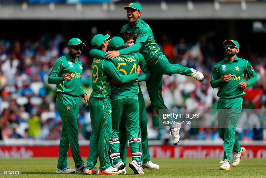 TOPSHOT - Pakistan's Mohammad Amir celebrates with teammates after taking the wicket of India's Shikhar Dhawan for 21 during the ICC Champions Trophy final cricket match between India and Pakistan at The Oval in London on June 18, 2017. Title-holders India were set a target of 339 to win the Champions Trophy final against Pakistan at The Oval on Sunday. / AFP PHOTO / Adrian DENNIS / RESTRICTED