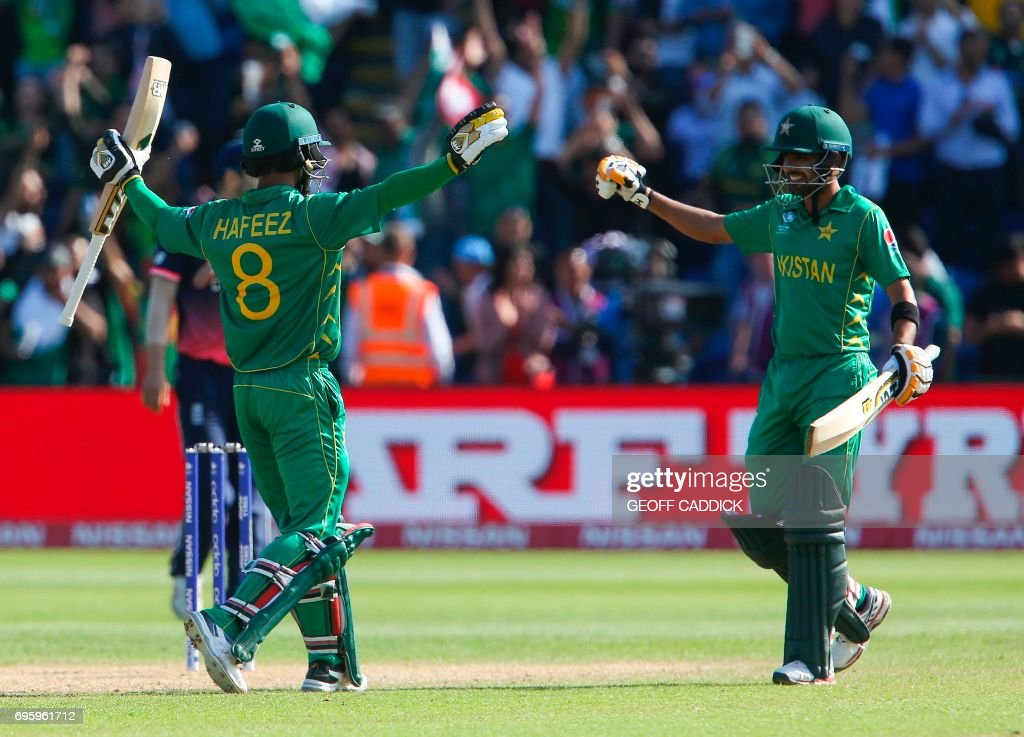Pakistan's Mohammad Hafeez (L) and Pakistan's Babar Azam celebrate after winning the ICC Champions Trophy semi-final cricket match between England and Pakistan in Cardiff on June 14, 2017. Set just 212 for victory, Pakistan finished on 215 for two, with Azhar Ali (76) and Fakhar Zaman (57) sharing an opening partnership of 118. / AFP PHOTO / Geoff CADDICK / RESTRICTED