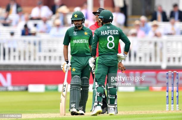 Pakistan's Mohammad Hafeez and Pakistan's Babar Azam speak on the wicket as they decide whether to appeal to the third umpire against a leg before...