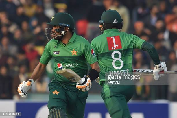Pakistan's Mohammad Hafeez and team captain Babar Azam take a run during the second T20 international cricket match of a threematch series between...