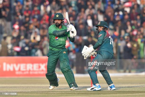 Pakistan's Mohammad Hafeez plays a shot as Bangladesh's Liton Das looks on during the second T20 international cricket match of a threematch series...