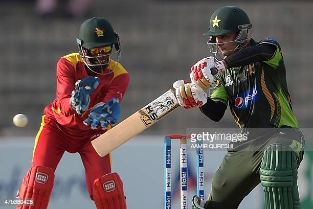 Pakistan's Mohammad Hafeez plays a shot as Zimbabwean wicketkeeper Richmond Mutumbami looks on during the third and final one day international match...