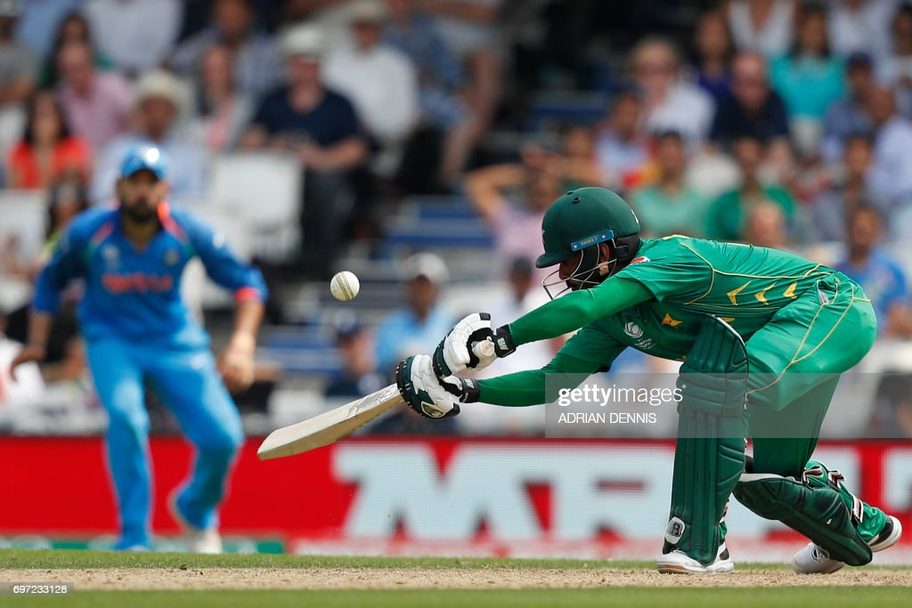 TOPSHOT - Pakistan's Mohammad Hafeez plays a shot during the ICC Champions Trophy final cricket match between India and Pakistan at The Oval in London on June 18, 2017. / AFP PHOTO / Adrian DENNIS / RESTRICTED
