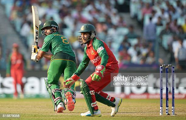 Pakistan's Mohammad Hafeezis watched by Bangladesh's wicketkeeper Mushfiqur Rahim as he plays a shot during the World T20 cricket tournament match...