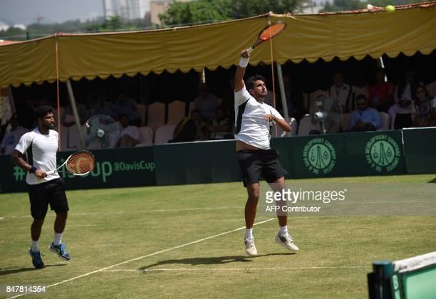 Pakistan's Muhammad Abid returns to Thailand's Ratiwana Sanchai and Ratiwana Sonchat during their Davis Cup AsiaOceania GroupII Tennis doubles match...